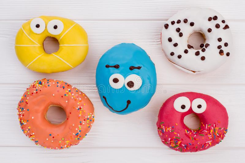 Assorted donuts on wooden background. Pastry with funny design. Dessert for a child stock image