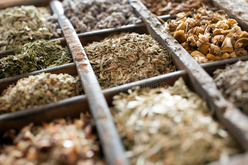 Assorted dried herbs in a printers tray. With focus to chamomile flowers and a blend of mixed herbs for use in the kitchen to season and flavour food stock photos