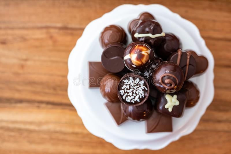 Assorted fancy milk and dark chocolate candy on a white cake plate on a wood background royalty free stock photos