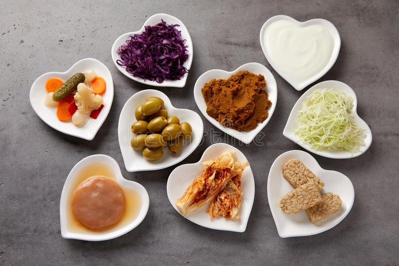 Assorted fermented foods viewed from above. In heart-shaped dishes with yogurt, beet, suaerkraut, scoby, pickles, miso and olives rich in probiotics and royalty free stock images