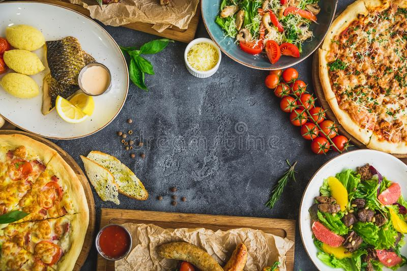 Assorted food set with copy space. Grilled pork ribs, pizza, salad, fish and sausages with fried potatoes. Tasty dishes on table. Top view stock photo
