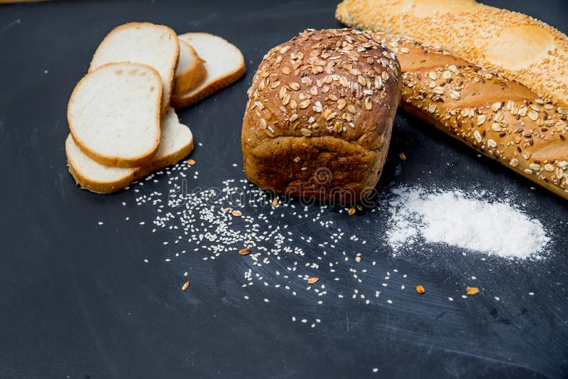 Assorted fragrant loaves of bread with flour. On a dark background stock photo