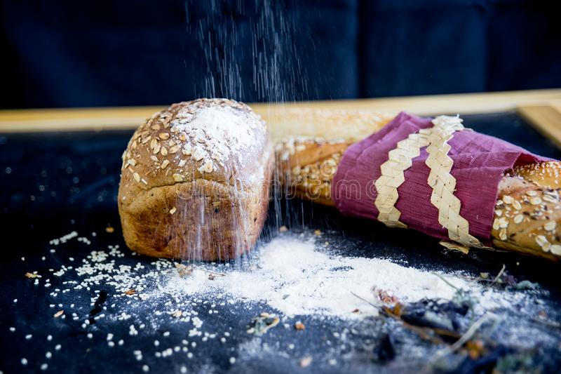 Assorted fragrant loaves of bread with flour. On a dark background royalty free stock photography