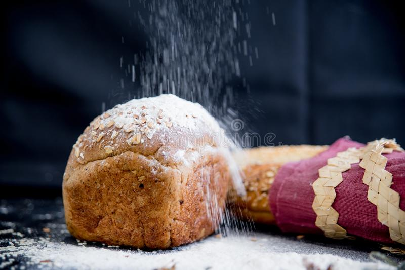 Assorted fragrant loaves of bread with flour. On a dark background stock images