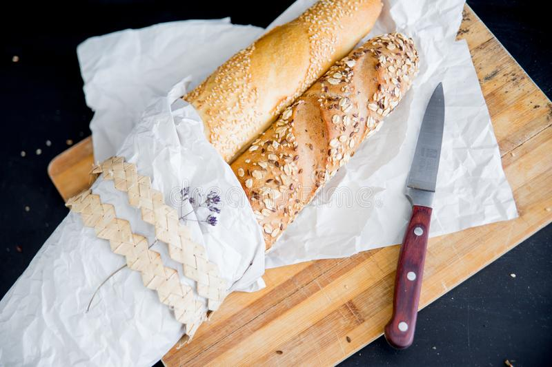 Assorted fragrant loaves of bread with flour. On a dark background royalty free stock image