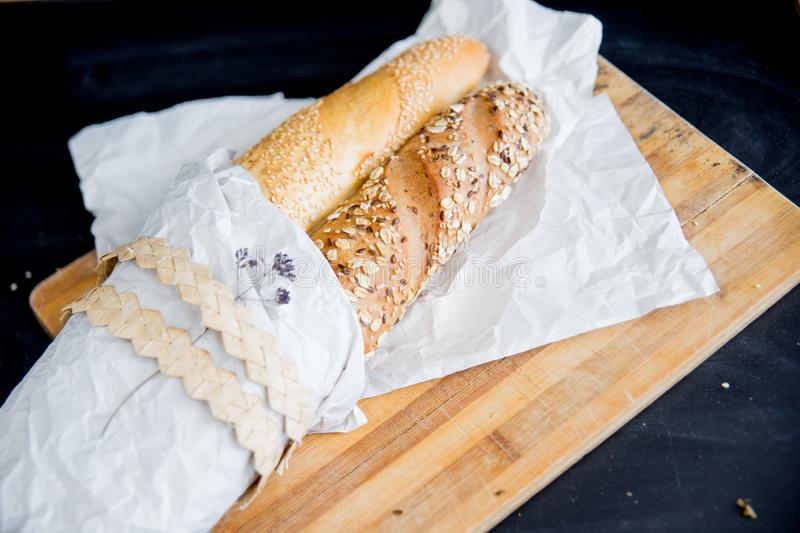 Assorted fragrant loaves of bread with flour. On a dark background stock photography