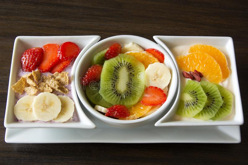 Assorted Fresh Fruit with Yogurt. Fresh fruit salad served along with strawberry greek yogurt topped with strawberries, cereal and bananas, and orange greek stock images
