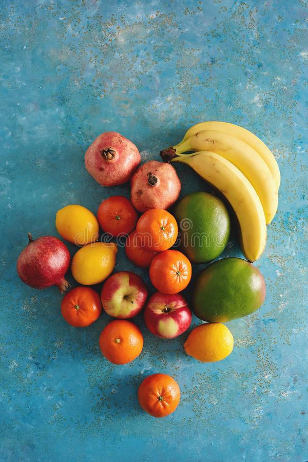 Variety of fresh fruits on rustic blue background. stock images