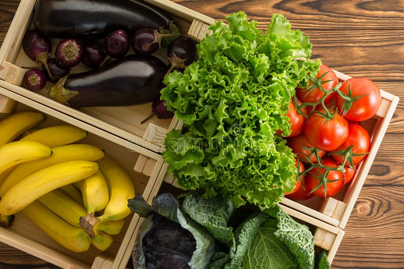 Assorted fresh organic vegetables in wooden boxes royalty free stock photography