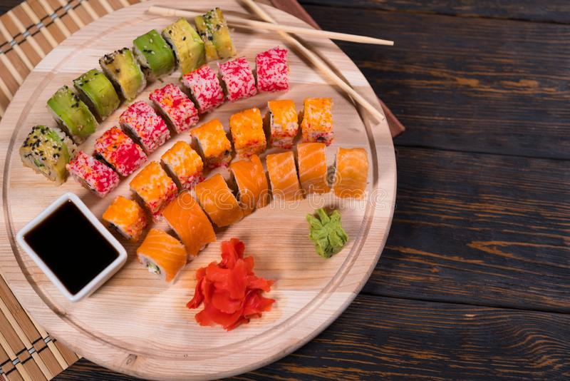 Assorted fresh sushi rolls on a wooden board royalty free stock photo