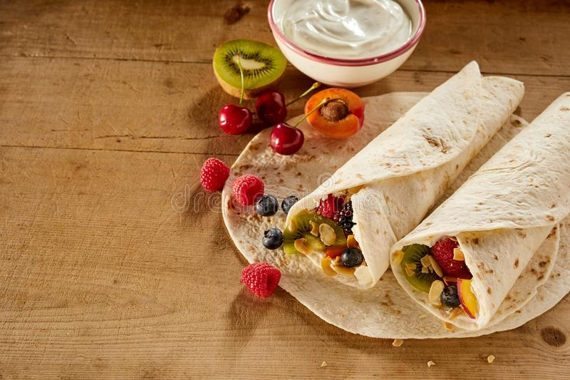 Assorted fresh tropical fruit in a wrap. Or pancake with whipped cream including kiwi, raspberry, blueberry, apple, apricot and cherries viewed high angle on a royalty free stock image