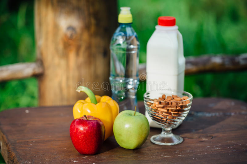 Assorted fresh vegetables, peppers, apples, water and milk on wooden table. yoga, life concept, healthy eating food. stock photography