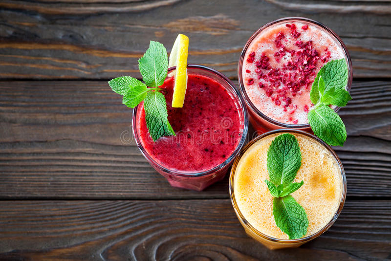 Assorted fruit smoothies on a wooden table royalty free stock image