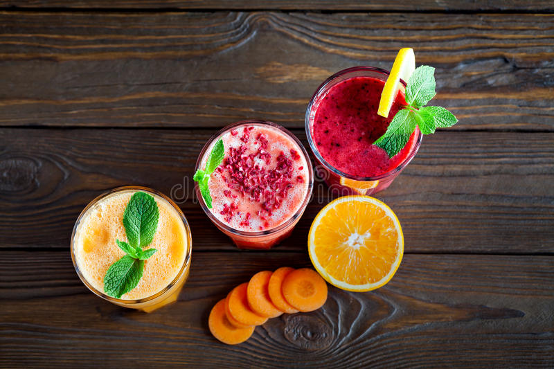 Assorted fruit smoothies on a wooden table royalty free stock photos