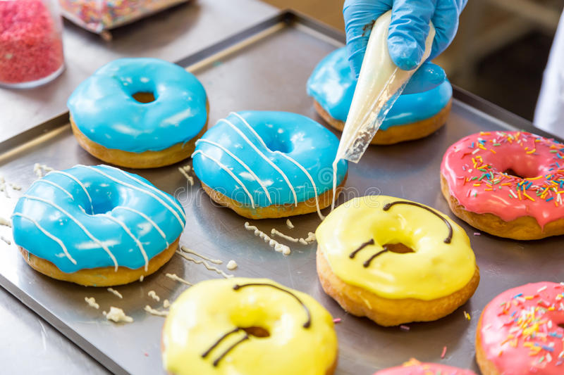 Assorted glazed doughnuts in different colors. On background royalty free stock photo