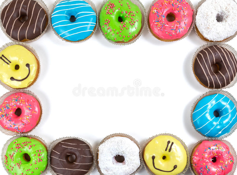 Assorted glazed doughnuts in different colors. Top frame from assorted glazed doughnuts in different colors on white background royalty free stock photography