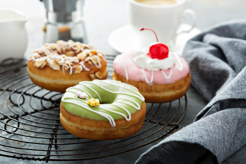 Sweet donuts on a cooling rack. Assorted glazed fried donuts with coffee for breakfast stock photo