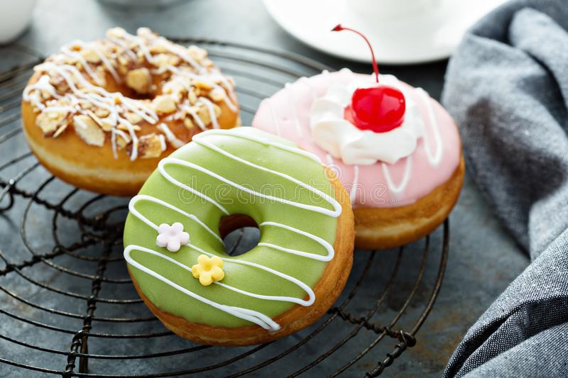 Sweet donuts on a cooling rack. Assorted glazed fried donuts with coffee for breakfast stock photography