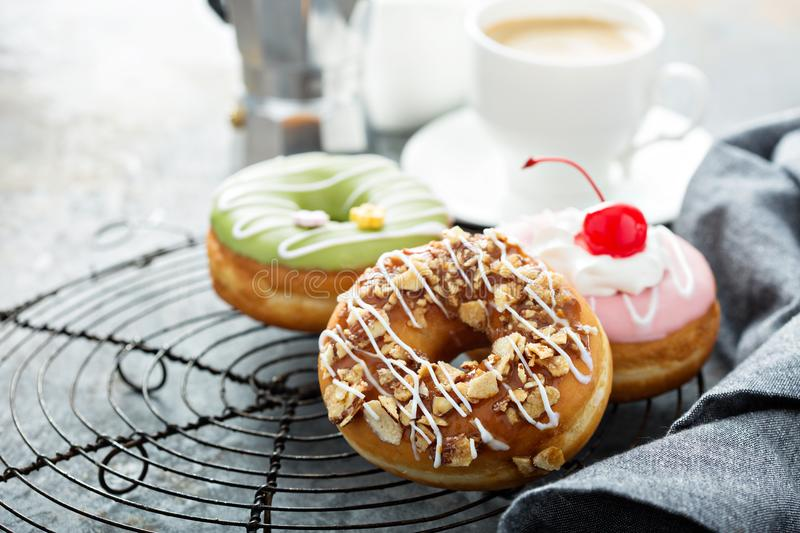 Sweet donuts on a cooling rack. Assorted glazed fried donuts with coffee for breakfast stock image