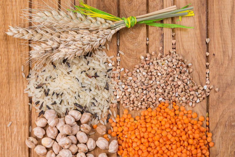 Assorted grains on wooden table. royalty free stock images