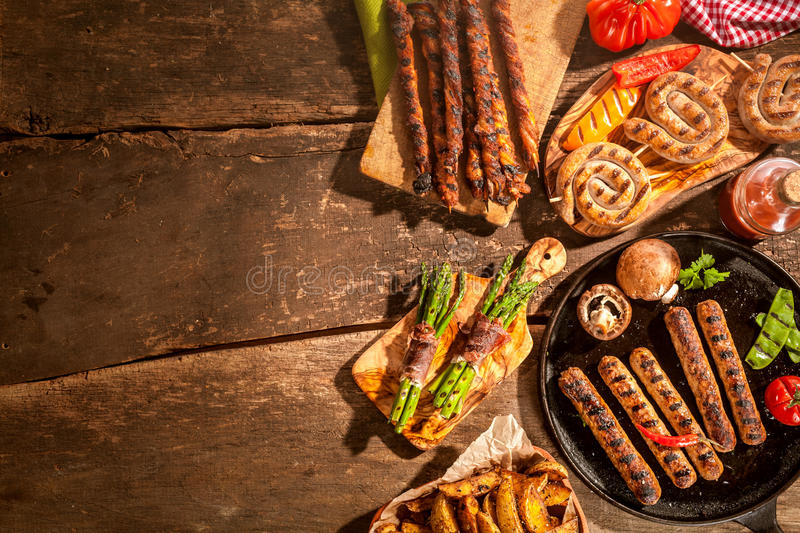Assorted grilled food from a summer barbecue. Assorted grilled food including sausages, potato wedges and asparagus bacon wraps from a summer barbecue on a royalty free stock photography