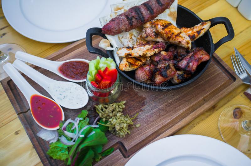 Assorted grilled meats and vegetables on a wooden table. Assorted delicious grilled meats and vegetables on a wooden table. Mixed grilled meat with sauces and stock images