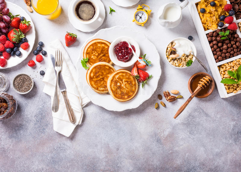 Assorted healthy breakfast. Healthy breakfast background with coffee, pancakes, fresh berries, quick cereals and orange juice, copy space, top view stock photos