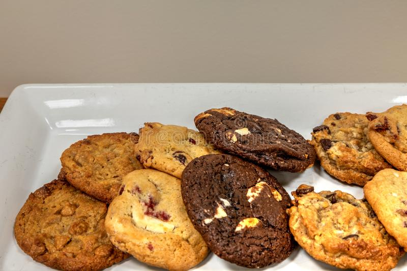 Assorted homemade cookies including chocolate chip, white chocolate chunk, oatmeal and peanut butter. Assorted homemade cookies on a white platter, including royalty free stock photo