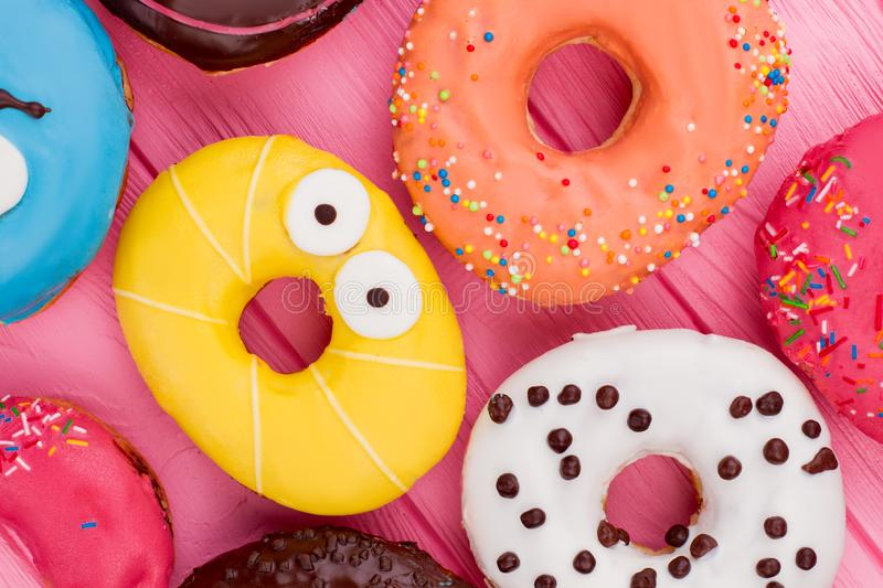 Assorted iced donuts background. Multicolored donuts close up. Delicious cakes with icing stock images