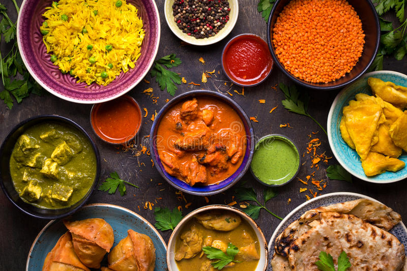 Assorted indian food. On dark wooden background. Dishes and appetizers of indian cuisine. Curry, butter chicken, rice, lentils, paneer, samosa, naan, chutney stock photo