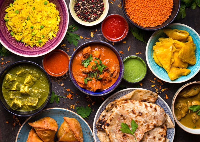 Assorted indian food. On dark wooden background. Dishes and appetizers of indian cuisine. Curry, butter chicken, rice, lentils, paneer, samosa, naan, chutney stock images