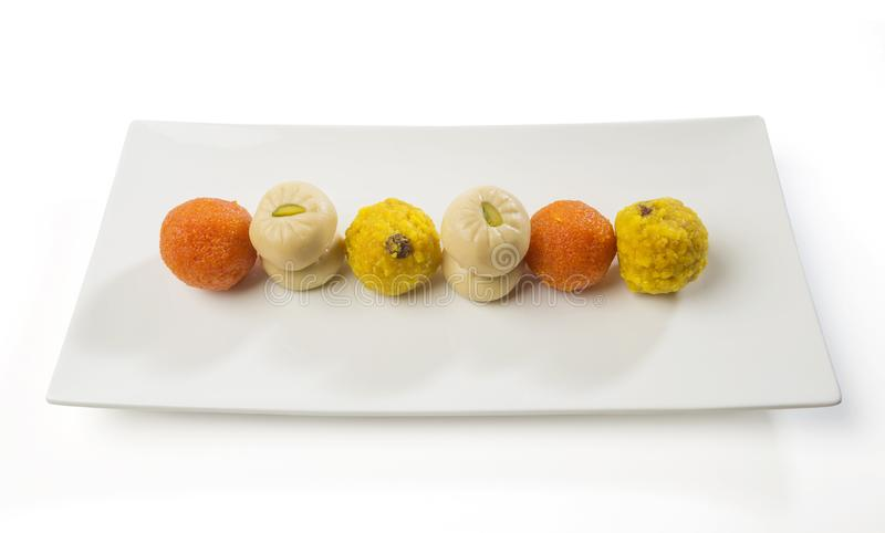 Assorted Indian sweets presented on a modern white platter. royalty free stock photography