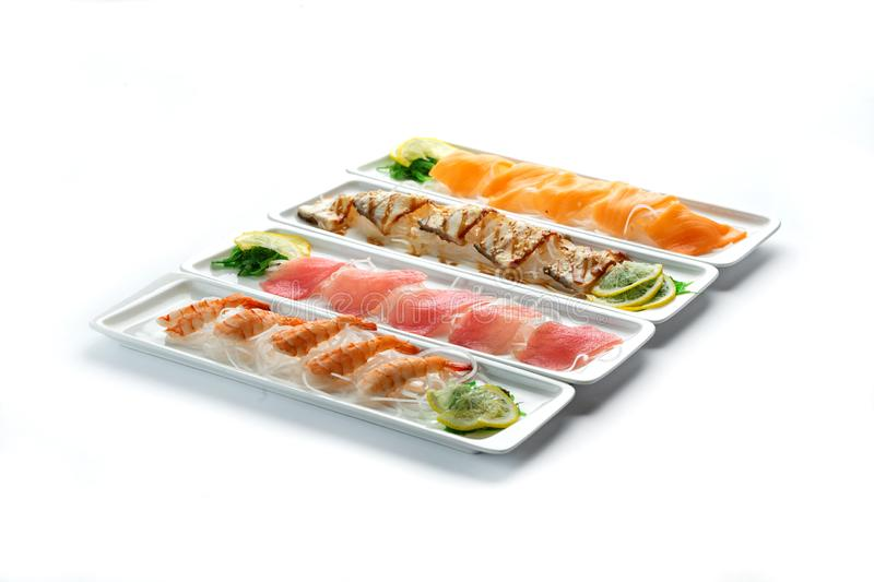 Assorted japanese food dishes on  plates on an isolated white background. Assorted japanese food dishes in a white rectangular plates on an isolated white royalty free stock image