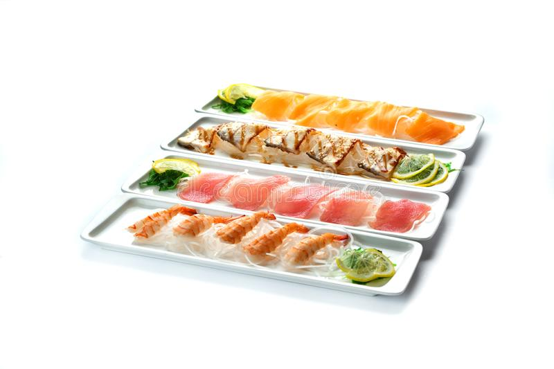Assorted japanese food dishes on  plates on an isolated white background. Assorted japanese food dishes on a white rectangular plates on an isolated white stock image