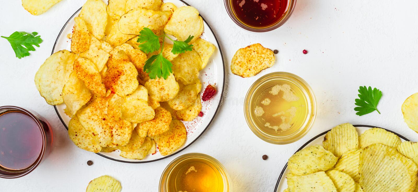 Assorted light and dark Beers and chips.  royalty free stock photography
