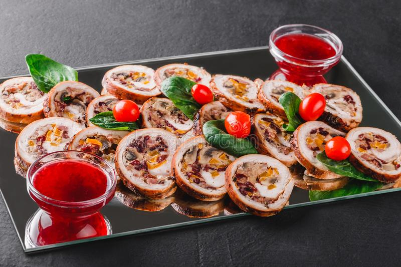 Assorted meat, stuffed chicken rolls, meat rolls stuffed with mushrooms, cranberries and dried apricots on black shale background royalty free stock photography