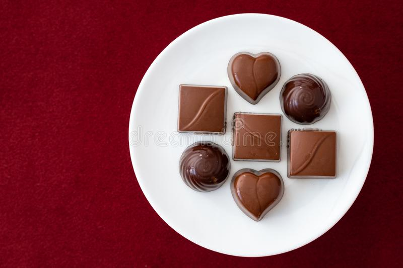 Assorted milk and dark chocolate candy on a white plate on a red background. For Valentine's Day royalty free stock photo
