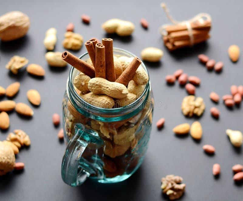 Assorted mischte Nüsse in einem Glasgefäß, in den Erdnüssen, in den Mandeln, in den Walnüssen und in den Samen des indischen Sesa stockbilder