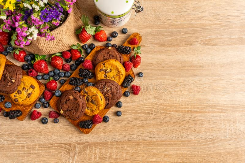 Assorted mix of cookies, wild berries and flowers royalty free stock photo