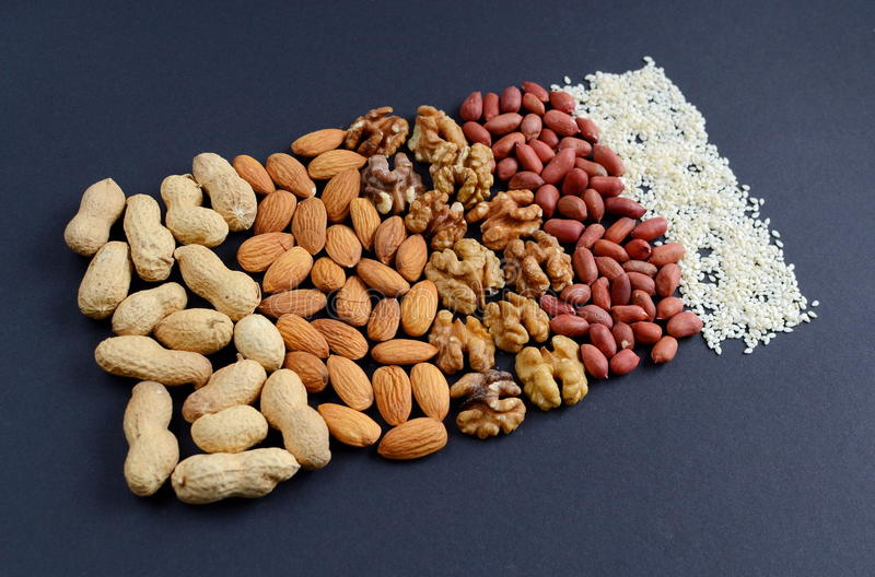 Assorted mixed nuts, peanuts, almonds, walnuts and sesame seeds. royalty free stock photos