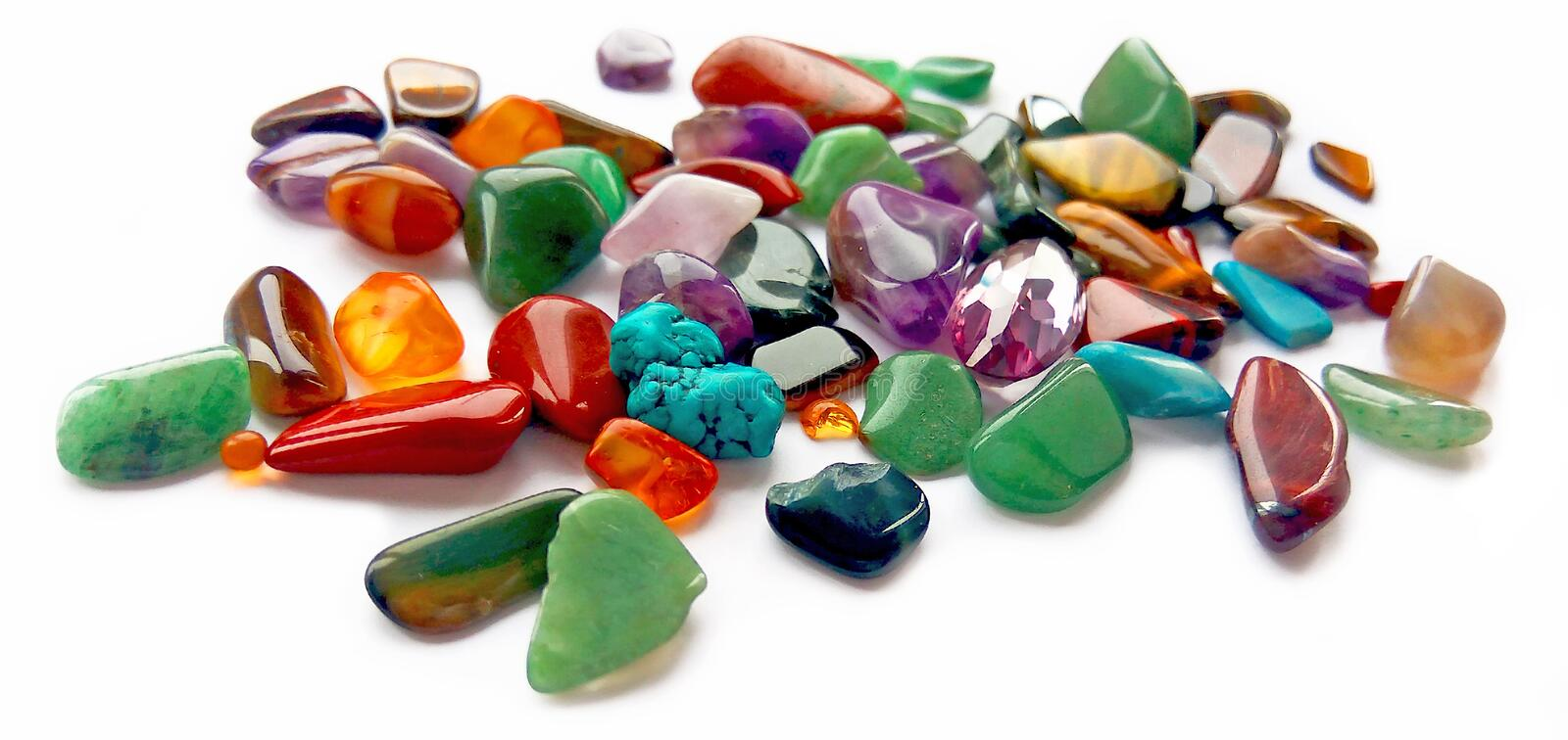 Assorted natural bright coloured semi precious gemstones and gems on white background stock images