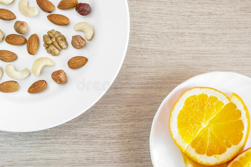 Assorted Nuts, Orange Slices On White Plates On Wooden Table. Healthy Organic Snack, Breakfast, Food Ingredients. Flat Lay Top-. Down Composition royalty free stock image