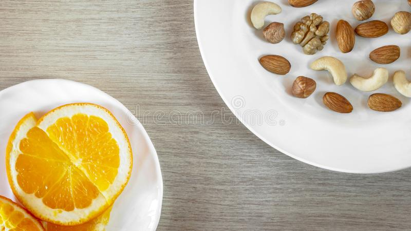 Assorted Nuts, Orange Slices On White Plates On Wooden Table. Healthy Organic Snack, Breakfast, Food Ingredients. Flat Lay Top-. Down Composition stock photography