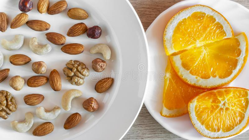 Assorted Nuts, Orange Slices On White Plates On Wooden Table. Healthy Organic Snack, Breakfast, Food Ingredients. Flat Lay Top-. Down Composition royalty free stock photo