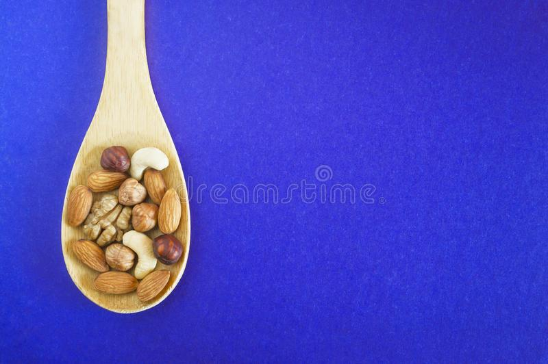 Assorted Nuts In A Wooden Spoon On Dark Blue Background. Healthy Organic Snack, Breakfast, Food Ingredients. Flat Lay Top-Down. Composition royalty free stock photos