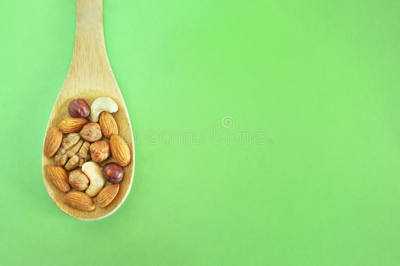 Assorted Nuts In A Wooden Spoon On Green Background. Healthy Organic Snack, Breakfast, Food Ingredients. Flat Lay Top-Down. Composition stock photo
