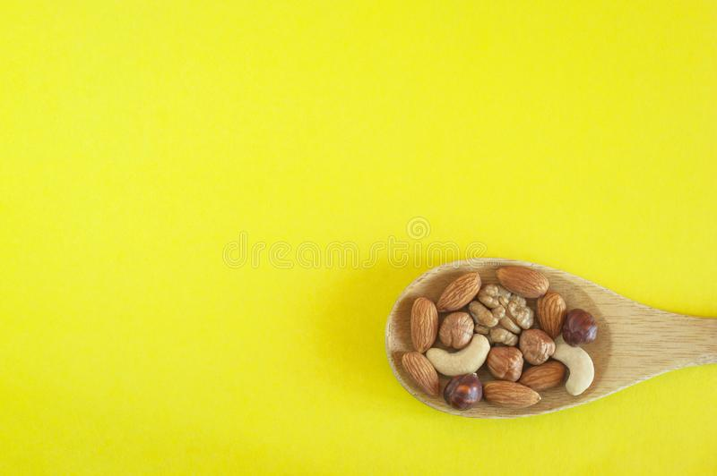 Assorted Nuts In A Wooden Spoon On Yellow Background. Healthy Organic Snack, Breakfast, Food Ingredients. Flat Lay Top-Down. Composition royalty free stock photos
