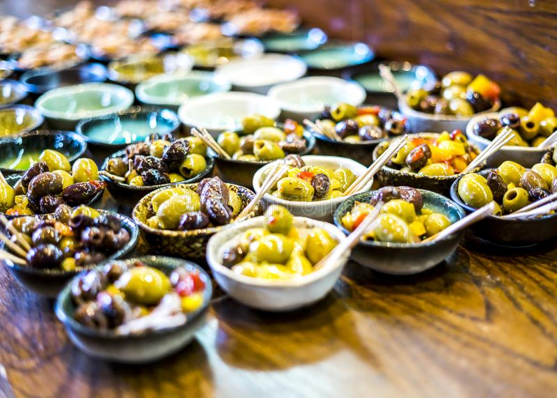 Assorted olives presented in a handmade pottery ramekins. Assorted oriental olive mix presented in a handmade pottery ramekins at a luxury bar setting as a bar royalty free stock photography