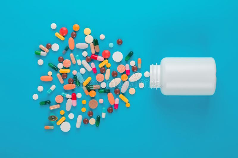 Assorted pharmaceutical medicine colored pills, tablets and capsules and bottle on blue background. royalty free stock photos