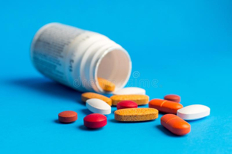 Assorted pharmaceutical medicine pills on blue background. Assorted pharmaceutical medicine pills, tablets and capsules bursting out of bottle royalty free stock image